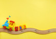 canvas print picture - Kids toy train with numbers on toy wooden railway on yellow background with copy space