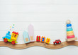 canvas print picture - Kids toys on toy wooden railway on white wooden background