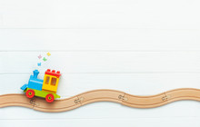 Kids Toy Train On Railway On White Wooden Background With Copy Space