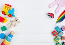 Frame Of Kids Toys On White Wooden Background With Copy Space