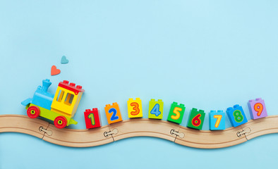 Kids toy train with numbers on toy wooden railway on light blue background with copy space