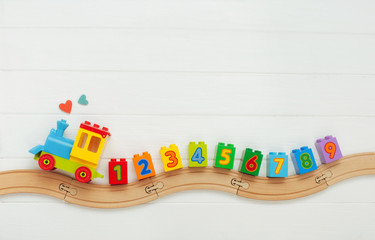 Kids toy train with numbers on railway on white wooden background with copy s...