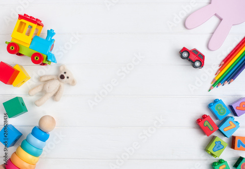 Obraz Frame of kids toys on white wooden background with copy space - fototapety do salonu