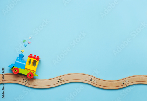 Fotografiet  Kids toy train on toy wooden railway on blue background with copy space