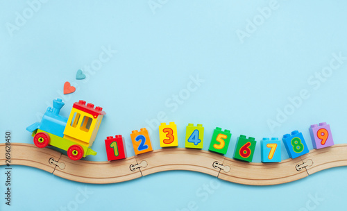 Fototapeta Kids toy train with numbers on toy wooden railway on light blue background with copy space obraz