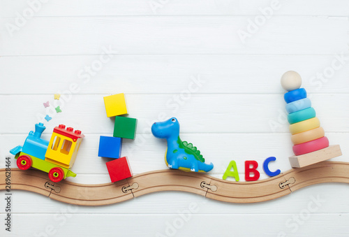 Kids toys on toy wooden railway on white wooden background with copy space