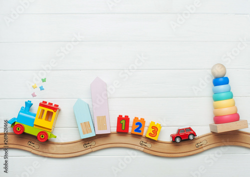 Obraz Kids toys on toy wooden railway on white wooden background - fototapety do salonu