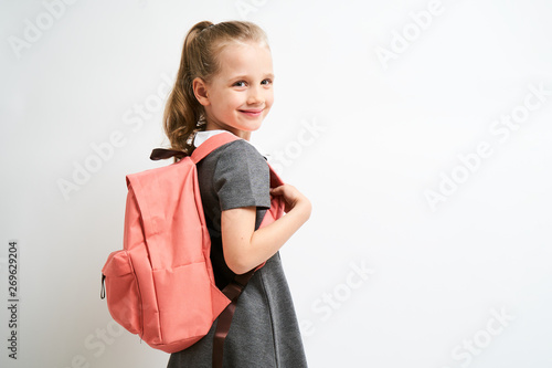 Obraz Little girl photographed against white background wearing school uniform dress isolated holding a coral backpack on both shoulders - fototapety do salonu