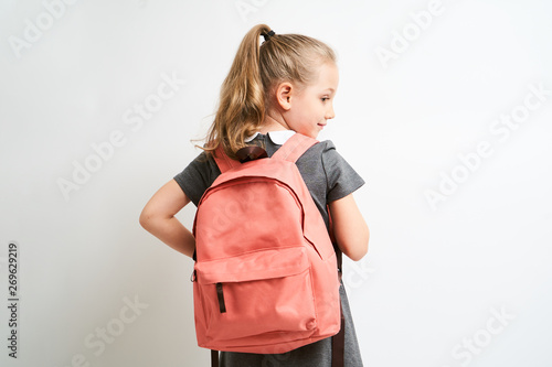 Fototapeta Little girl photographed against white background wearing school uniform dress isolated holding a coral backpack on both shoulders obraz