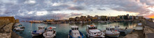 Heraklion, Crete Island / Greece. Panoramic View Of The Old Venetian Port With The Fortress Koules (Castello A Mare) And The Heraklion City At Sunset Time With Cloudy Sky. Traditinal Fishing Boats