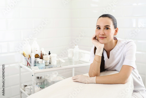 Beautician doctor sitting near couch at beauty clinic office Wallpaper Mural