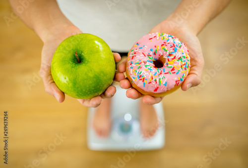 Fotografia  Woman on scale measuring weight holding apple and donuts choosing between health