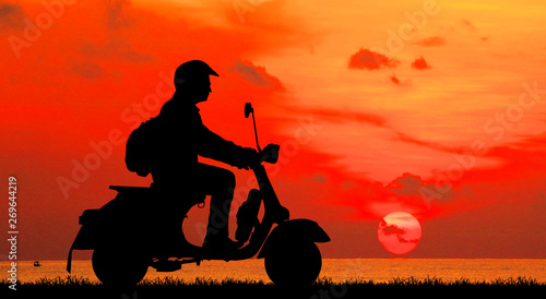 Foto auf Leinwand Rot Silhouette biker with his motorbike on blurry blue sky background