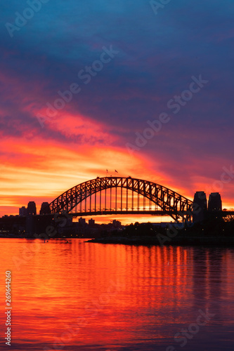 Silhouette of Sydney Harbour Bridge with orange burning sky at dawn.