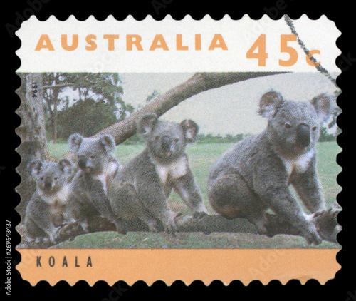 Fotografia  AUSTRALIA - CIRCA 1994: post stamp printed in Australia shows four koalas on tre