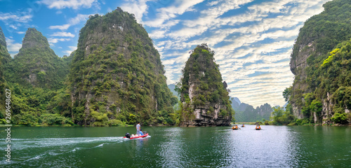 Fotografie, Obraz  Ninh Binh, Vietnam - April 5th, 2019: People rowing boats for carrying tourists on Ngo Dong river of the Tam Coc National Park