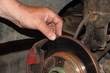 Test of thickness of the brake disk, car diadnostics - man hand points your fingers at the unventilated brake disc