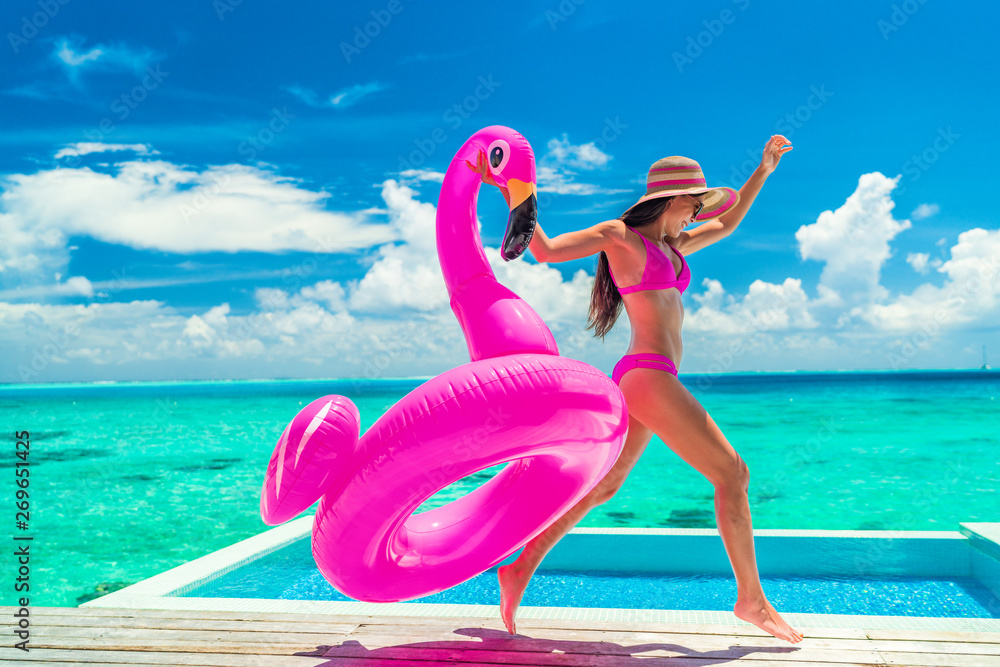 Fototapeta Vacation fun woman in bikini with funny inflatable pink flamingo pool float running of joy jumping by infinity swimming pool. Girl enjoying travel holidays at resort luxury overwater bungalow travel.