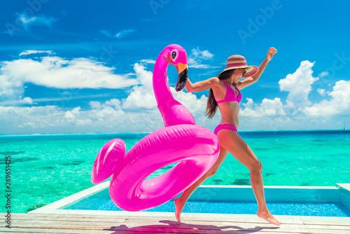 obraz dibond Vacation fun woman in bikini with funny inflatable pink flamingo pool float running of joy jumping by infinity swimming pool. Girl enjoying travel holidays at resort luxury overwater bungalow travel.