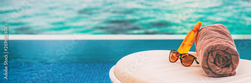 Obraz Luxury vacation banner background of sunscreen, sunglasses for sun protection on towel and lounger at hotel infinity swimming pool for sun tan summer relaxation panoramic banner. - fototapety do salonu