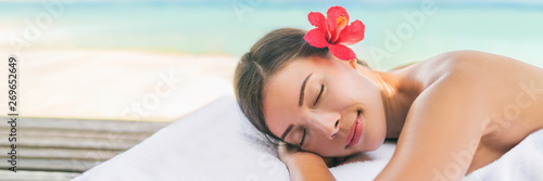 Spa massage therapy woman lying on massage table for full body scrub or deep tissue swedish luxury treatment. Banner panoramic background.