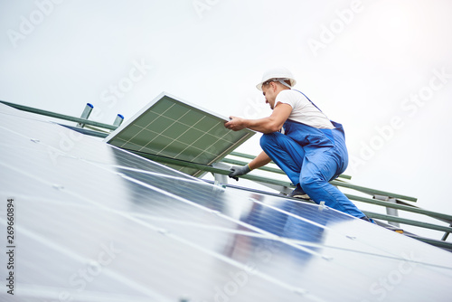 Installing of solar photo voltaic panel system. Professional worker in hard-hat and blue overall lifting the solar module on metal platform. Alternative energy and professional construction concept.