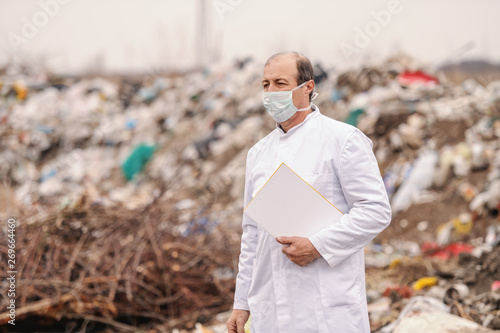 Valokuva  Caucasian ecologist in white uniform holding clipboard under armpit, walking on landfill and estimating pollution