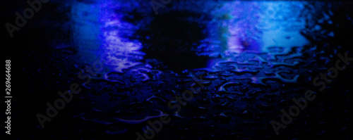 Photo sur Toile Les Textures Wet asphalt, night scene of an empty street with a little reflection in the water, the night after the rain. Abstract dark neon background with a wet surface, reflection, neon, glare, blurred bokeh.