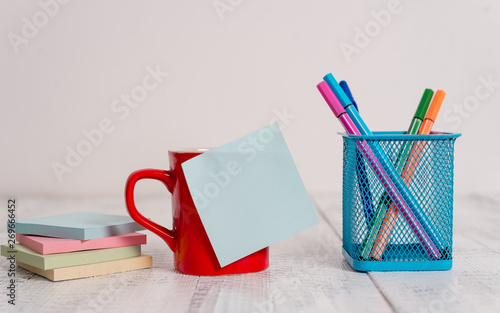 Fotografie, Obraz  Coffee cup blank sticky note pens metal holder stacked pads wooden table