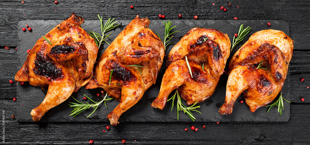 Fototapety, obrazy: Halves of appetizing grilled juicy chicken with golden brown crust served with lemon slices,barbeque  sauce and rosemary.