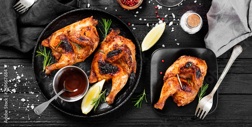 Fototapeta Halves of appetizing grilled juicy chicken with golden brown crust served with lemon slices,barbeque  sauce and rosemary. obraz