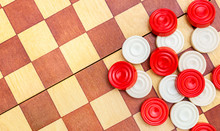 Heap Of Different Checkers On Wooden Checkerboard. Space For Text. Top View.Heap Of Different Checkers On Wooden Checkerboard. Space For Text. Top View.