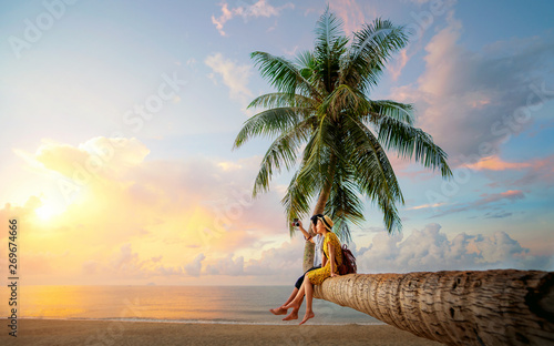 Asian couple selfie by camera on coconut palm tree in Kho Mak island Wallpaper Mural