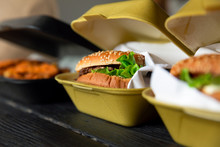 Hamburger In A Takeaway Container On The Wooden Background. Food Delivery And Fast Food Concept