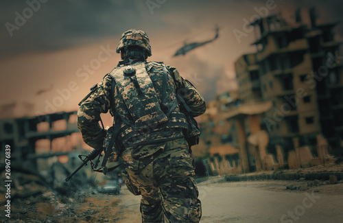 Obraz Soldier running in destroyed city to reach the helicopter to escape - fototapety do salonu