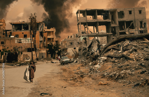 Cuadros en Lienzo Homeless little girl walking in destroyed city that was bombed by the enemy and she's looking for shelter
