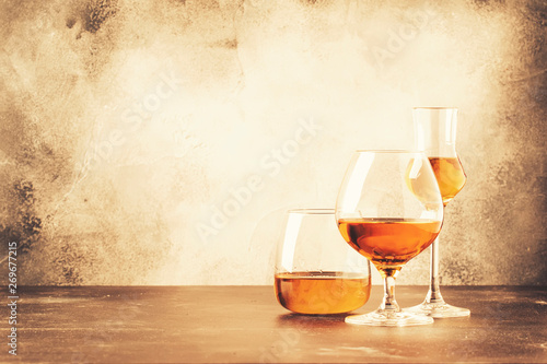Fotobehang Alcohol Selection of hard strong alcoholic drinks and spirits in assortment: cognac, brandy and rum. Gray bar counter background, selective focus, copy space