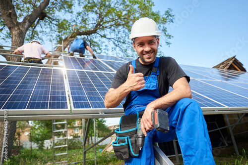 Portrait of smiling technician with electrical screwdriver showing thumb-up in front of unfinished high exterior solar panel photo voltaic system with team of workers on high platform Fototapeta