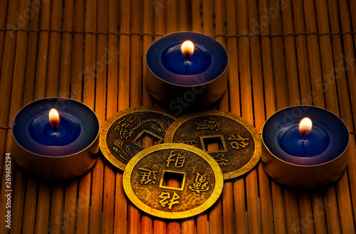 Old china chinese lucky Feng shui coins with three candles Fototapeta