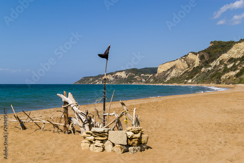 Paradise sandy beach without people with a black (pirate) flag Canvas Print