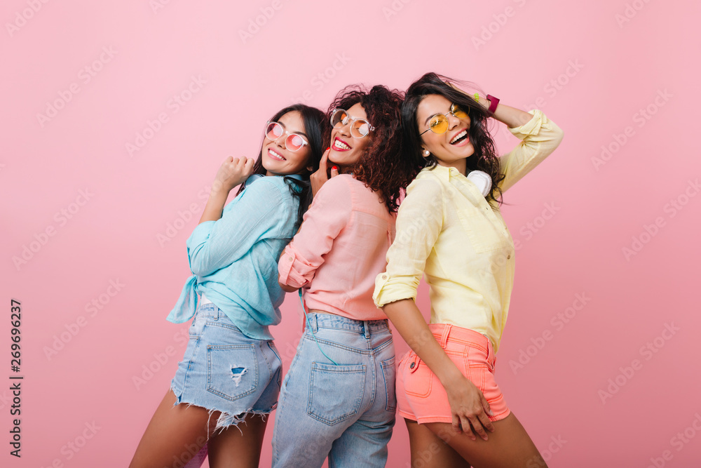 Fototapety, obrazy: Carefree girls in colorful cotton shirts posing together and smiling. Indoor portrait of attractive young ladies expressing happy emotions during joint photoshoot.