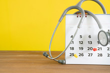 Stethoscope And Calendar On The Table With Yellow Background, Schedule To Check Up Healthy Concept