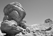 Black & White Looming Formation In Foreground Resembling Balanced Rocks With Isolated Mesa On The Right.