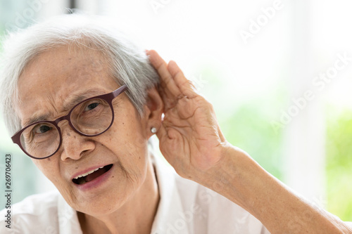 Valokuva  Asian senior woman listening by hand's up to the ear,having difficulty in hearin