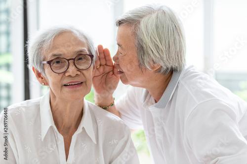 Valokuvatapetti Asian senior woman holding hand  telling funny,gossips on ears to friend,speakin