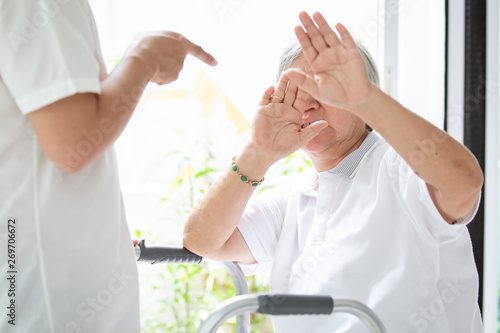 Photo Asian elderly woman were physically abused,attacking in house,angry man raised punishment fist,stop physical abuse senior people,caregiver,family stop violence and aggression concept