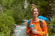 Leinwandbild Motiv Positive female tourist wanders near mountain river in wood, poses against nature composition, focused aside gladfully, drinks hot beverage, dressed in orange jumper. People and adventure concept