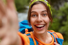 Close Up Shot Of Happy European Female Smiles Broadly At Unrecognizable Device, Makes Travel Selfie, Wears Rucksack, Poses Over Nature Background, Has Fun Outdoor, Being On Holiday, Does Self Portrait