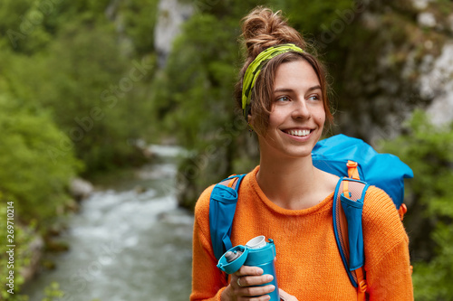 фотографія  Glad tourist recreats in mountains near small river, green trees, focused aside with broad smile, dressed in casual clothes, has big rucksack on shoulders, drinks aromatic bevergae from flask