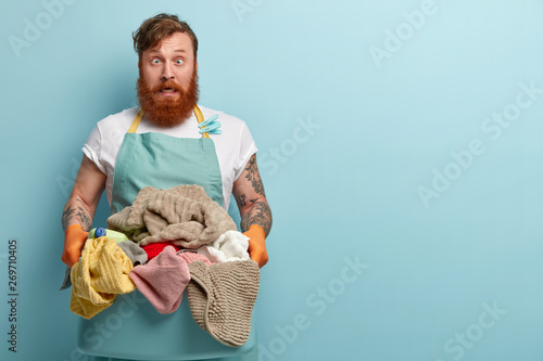 Fotografie, Obraz  Crazy redhead man foolishes indoor, crosses eyes, wears casual apron and rubber